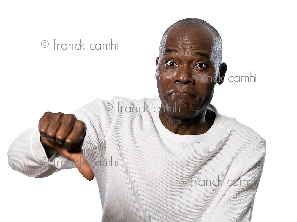Portrait of a displeased afro American man showing thumbs down sign in studio on white isolated background