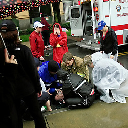 Kyle Green | The Roanoke Times<br /> 4/16/2011 A woman cries (middle, red jacket) as her father, a 1/2 marathon participant,  is tended to by paramedics after he collapsed near the finish line of the 2011 Blue Ridge Marathon in Roanoke, Virginia. &quot;The runner who fell was breathing on his own at last check,&quot; a marathon organizer, John Carlin, told the finish line crowd later.