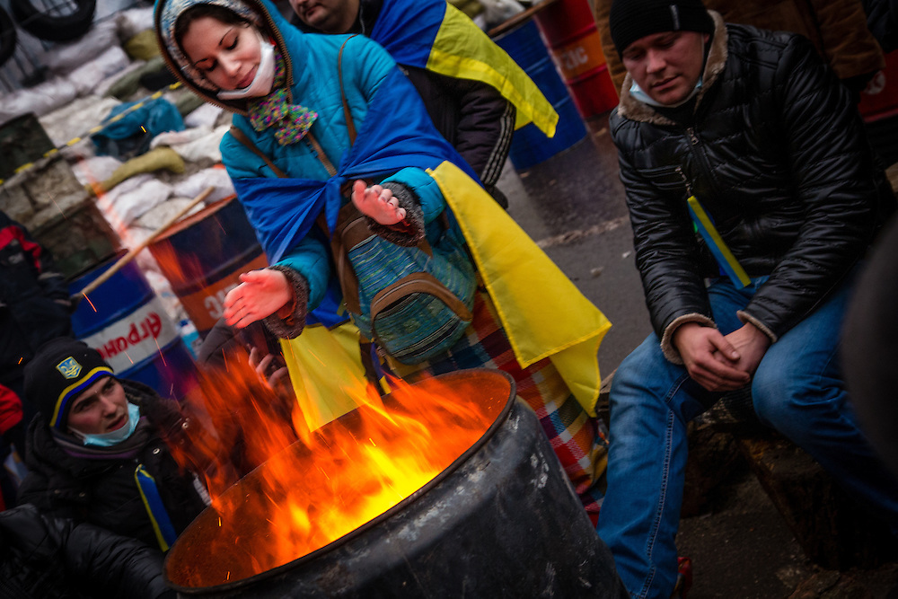 A young woman heats her hands next to a brasero on the Independance Square.
