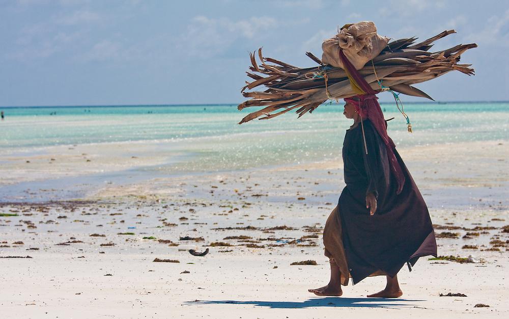 Woman carrying wood down Paje beach, Zanzibar
