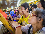 30 OCTOBER 2014 - BANGKOK, THAILAND: People leave prayers and wishes on the red cloth that will placed on the chedi at Wat Saket before the parade marking the start of the temple's annual temple. Wat Saket is on a man-made hill in the historic section of Bangkok. The temple has golden spire that is 260 feet high which was the highest point in Bangkok for more than 100 years. The temple construction began in the 1800s in the reign of King Rama III and was completed in the reign of King Rama IV. The annual temple fair is held on the 12th lunar month, for nine days around the November full moon. During the fair a red cloth (reminiscent of a monk's robe) is placed around the Golden Mount while the temple grounds hosts Thai traditional theatre, food stalls and traditional shows.   PHOTO BY JACK KURTZ