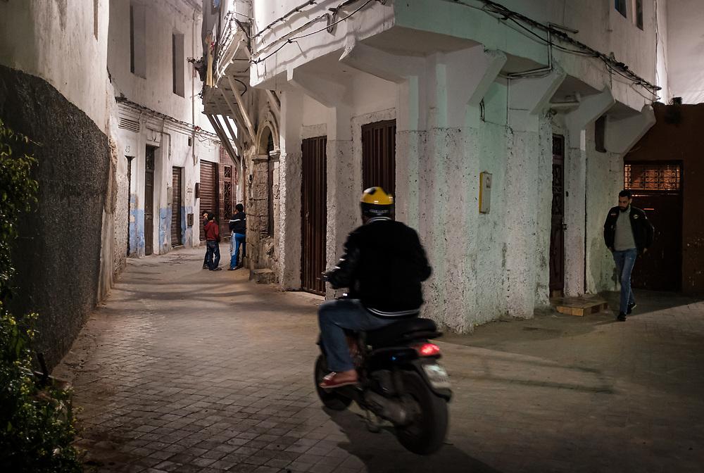CASABLANCA, MOROCCO - CIRCA APRIL 2018: Man riding a motorcycle in he streets of the medina of Casablanca at night.
