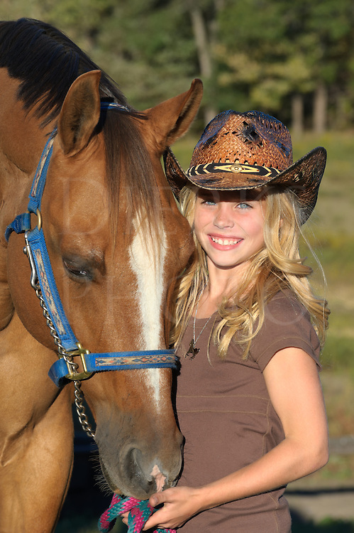 Girl with horse in close up portrait, pretty blonde in cowboy hat in summer evening sunlight in Pennsylvania, PA, USA.