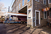 Papoose, Herreshoff S Class, exits the Bristol Boat Company building after a complete restoration.