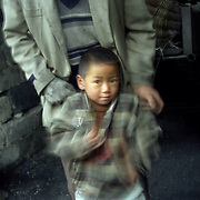 Young child with his father working in selling unrefined coal.