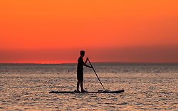 © Licensed to London News Pictures. 02/07/2018. Aberystwyth, UK. A paddle boarder at sunset in Aberystwyth at the end of yet another hot and cloudless day, as the prolonged heatwave continues to dominate the weather over the UK. Photo credit: Keith Morris/LNP