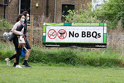 © Licensed to London News Pictures. 10/05/2020. London, UK. A couple walk past 'No BBQ' sign in London Fields park in Hackney, north London. Later today, Prime Minister Boris Johnson is set to announce measures to ease the coronavirus lockdown, which was introduced on 23 March to slow the spread of the COVID-19. Photo credit: Dinendra Haria/LNP
