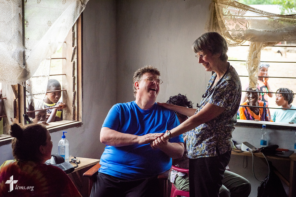 The Rev. Michael Awe, team leader and pastor at Hope Lutheran Church, South Sioux City, Neb., laughs with Bonnie Hartman, a member of Faith Lutheran Church, Godfrey, Ill., as the clinic wraps up on the fifth day of the LCMS Mercy Medical Team on Friday, May 11, 2018, in the Yardu village outside Koidu, Sierra Leone, West Africa. LCMS Communications/Erik M. Lunsford
