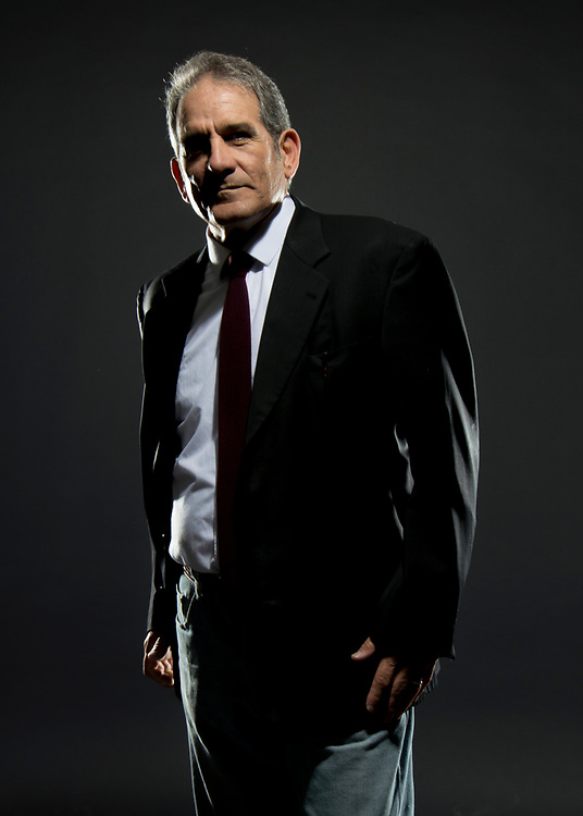 Gentleman model posing in a dark suit with white dress shirt against a black background.