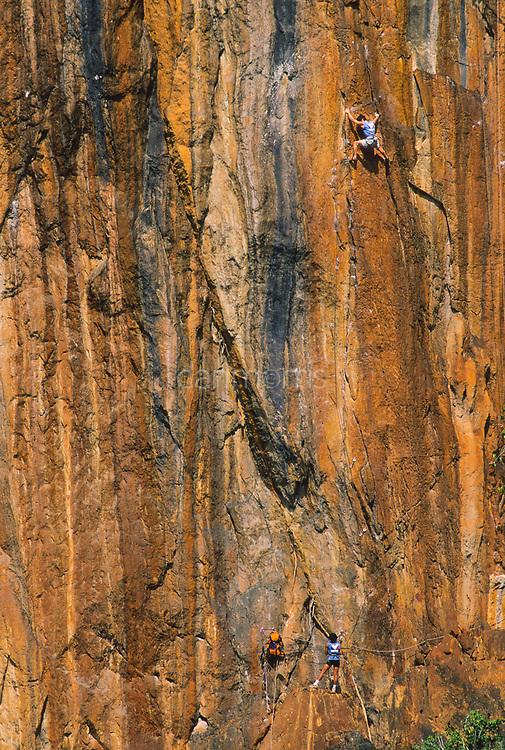 Tamotsu Sugino climbs orange limestone on Mr. Thavidet, 5.12b, Ban Pak Ou, Luang Phrabang, Laos
