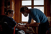 A medical doctor examines a pensioneer  during a home visit in Oberursel, wearing a mouth protection because of the coronavirus danger.