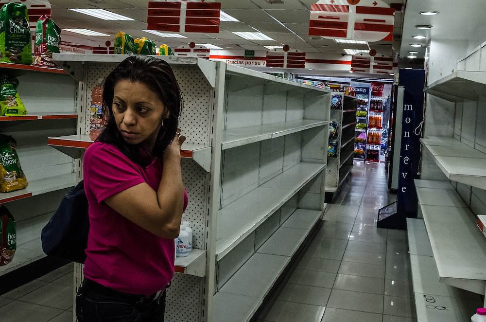 CARACAS, VENEZUELA - JANUARY 21, 2015: Empty shelves in a privately owned pharmacy where toilet paper, laundry detergent and sanitary pads should be. Despite being a petro-state with one of the largest oil reserves in the world, basic food goods, medicines and personal hygiene items such as soap, toilet paper and shampoo, are difficult to find in stores across Venezuela.
