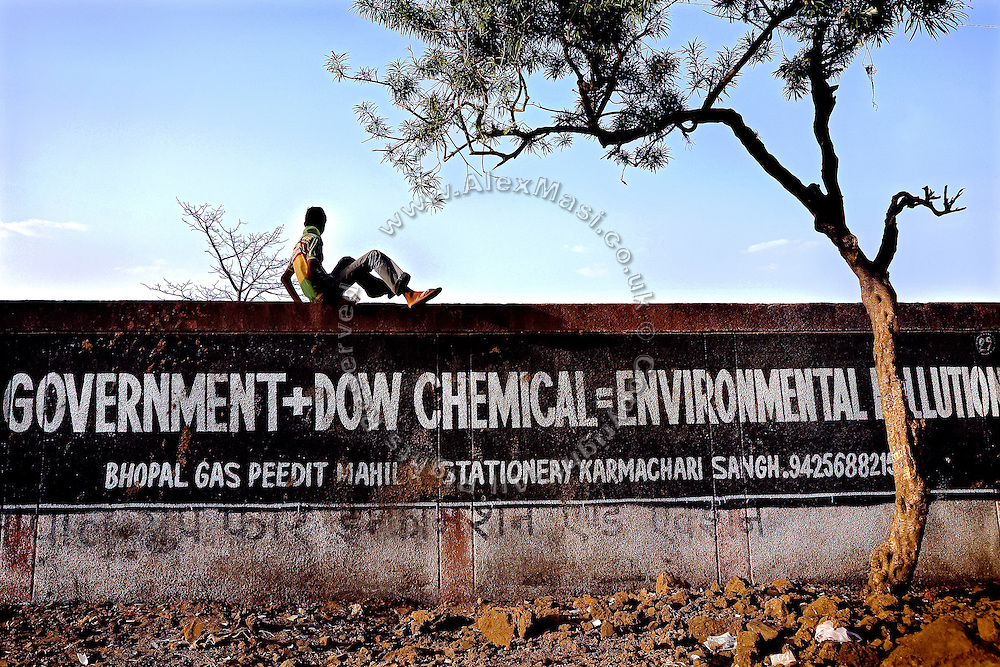 A boy is jumping over the wall of the abandoned Union Carbide (now DOW Chemical) industrial complex. Many of the walls surrounding Union Carbide have been covered in graffiti such as this one, in Bhopal, Madhya Pradesh, India, site of the infamous 1984 gas disaster.