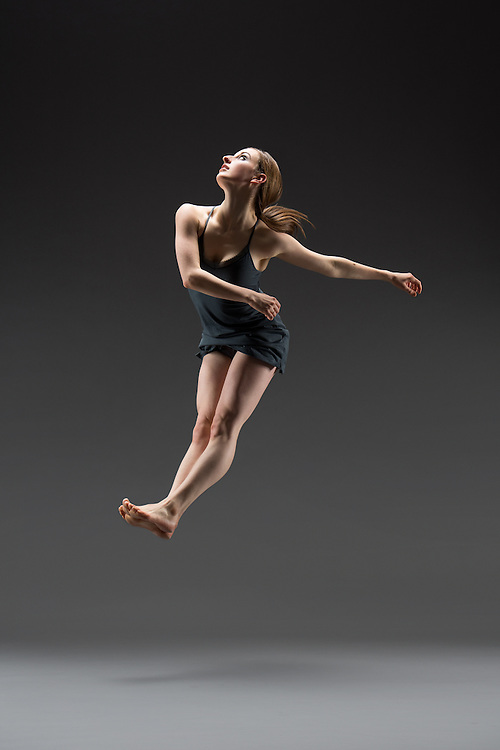 Contemporary female dancer, Molly Levy, jumping, taken in the photo studio on a dark background. Photograph taken in New York City by photographer Rachel Neville.