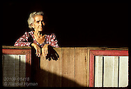 Elderly woman gazes from front porch of her modest home in the jungle town of Eirunepe, AM. Brazil