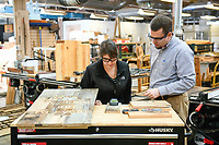 Faculty and students look over wood products in Hodges lab.