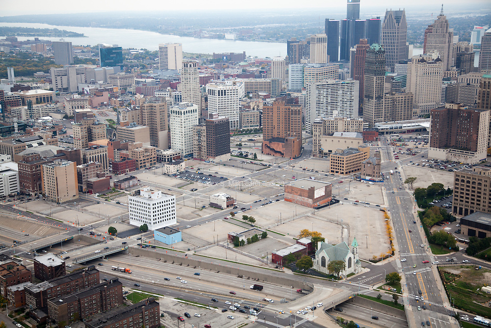 The Fisher Freeway (bottom) meets Grand River Avenue (right), leading in to downtown Detroit. This area on the edge of downtown hosts more empty lots than buildings, a majority of which serve as gravel or macadam surface parking.