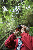 Senior man in forest looking up with binoculars