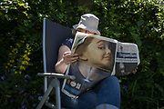 A middle-aged lady reads the Guardian newspaper featuring a toothbrush ad and Prime Minister Theresa May with the headline 'Hubris and Humiliation' in a shady spot of her summer garden, Two days after the 2017 general election, on 10th June 2017, in London, England.