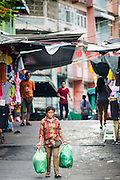 06 JUNE 2013 - BANGKOK, THAILAND:     A woman walks to Bobae Market in Bangkok. Bobae Market is a 30 year old market famous for fashion wholesale and is now very popular with exporters from around the world. Bobae Tower is next to the market and  advertises itself as having 1,300 stalls under one roof and claims to be the largest garment wholesale center in Thailand.       PHOTO BY JACK KURTZ