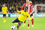Arsenal midfielder Bukayo Saka (77) goes down under pressure from Sheffield United forward Oli McBurnie (9)  during the Premier League match between Sheffield United and Arsenal at Bramall Lane, Sheffield, England on 21 October 2019.