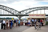 Europa, Deutschland, Koeln, die aus dem Koelner Tatort ARD Krimiserie bekannte Wurstbraterei der Familie Vosen im Rheinauhafen, im Hintergrund die Suedbruecke.<br /> <br /> Europe, Germany, Cologne, hot-dog stall at the Rheinau harbor, known from the TV series Tatort, in the background the South Bridge.