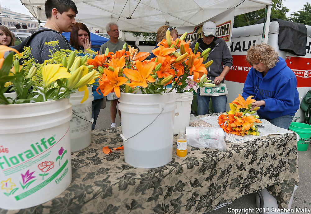 Christy Hodnefield (right), of Pheasant Run Farm, wraps flowers for a customer at the Downtown Farmers' Market in Cedar Rapids on Saturday morning, June 2, 2012. There were 244 vendors who participated in the first market of the year. (Stephen Mally/Freelance)
