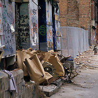Garbage is piled and packed in paper sacks in front of abandoned buildings in Manhattan's Lower East Side in the 1980s.