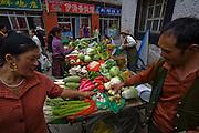 People shop for vegetables at a market in Lhasa, Tibet.
