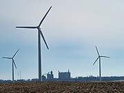 "24 FEBRUARY 2020 - BLAIRSBURG, IOWA:  Wind turbines on a ""wind farm"" near Blairsburg. The grain elevator in Blairsburg is in the background. There are more than 100 wind turbines at this location. In 2019, Iowa generated more than 41% of its electrical needs with wind power. Iowa is the 2nd leading producer of wind energy in the US, only Texas generates more electricity by wind power. There are more than 4,500 wind turbines in Iowa.      PHOTO BY JACK KURTZ"