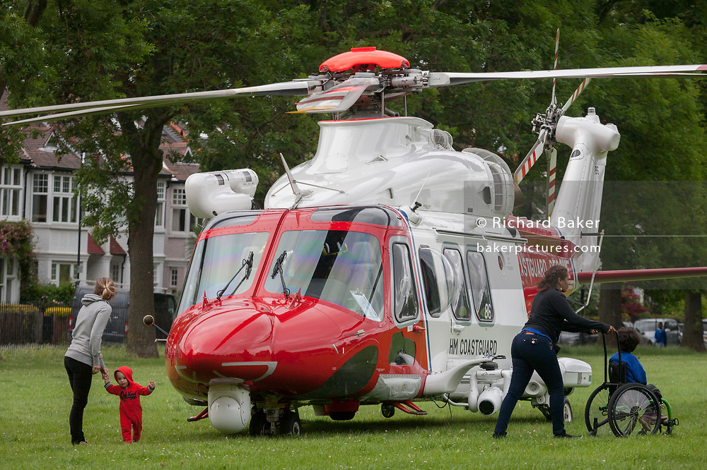 Local residents look closely at an AgustaWestland AW139 helicopter operated by the UK Coastguard rescue which is briefly landed in Ruskin Park to deliver an emergency patient, on 8th June 2017, in the south London borough of Lambeth, England. The AW139 is used by Her Majesty's Coastguard (HMCG) which is a section of the Maritime and Coastguard Agency responsible for the initiation and co-ordination of all maritime search and rescue (SAR) within the UK Maritime Search and Rescue Region.