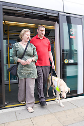 Vision impaired man with sighted guide and guide dog walking alighting from a tram on to the platform,