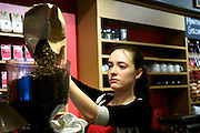 February 14, 2011 - Sheena Gibbs, a barista at Expresso Royale Coffee in Boston, MA, pours coffee beans into a grinder. Photo by Lathan Goumas.