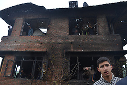 May 24, 2019 - Srinagar, Kashmir, India - May 24, 2019 - Noorpora, Jammu And Kashmir, India - Kashmiri people inspect the war ravaged house. Thousands of Kashmiri's attended the funeral of militant comander Zakir Musa killed in an eleven hour long gun battle in Noorpora area of Pulwama district of Indian controlled Kashmir. (Photo by  Masrat Zahra/NUR photo) (Credit Image: © Masrat Zahra/NurPhoto via ZUMA Press)