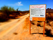 July 12 - GILA BEND, AZ: Signs warning recreational users of the Sonoran Desert National Monument of the dangers of encountering illegal immigrants and drug smugglers on BLM Road 8018c south of Gila Bend, AZ, off of Interstate 8. The Bureau of Land Management (BLM) put up the signs at entrances to the Sonoran Desert National Monument after off roaders reported being shot at by unknown parties and a deputy from the Pinal County Sheriff's Department was fired on and nearly killed by suspected drug dealers. The signs have ignited a firestorm in Arizona politics, conservatives and anti-immigration activists assert that the signs are proof that illegal immigration and drug smuggling is out of control in the area while others suggest that the danger is overstated and the signs are hurting Arizona tourism. A BLM spokesperson said no one has been hurt in the area by confirmed smugglers and that there are very few encounters between smugglers and tourists or off roaders in the monument.    Photo by Jack Kurtz  PHOTO ILLUSTRATION, MANIPULATED WITH SOFTWARE