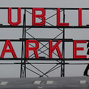 An umbrella-toting pedestrian crosses Pine Street along 1st Avenue in dowtown Seattle Wednesday Jan. 14, 2004 during a dreary winter day in front of one of the Pike Place Market's signature neon signs.  Joshua Trujillo / Seattle Post-Intelligencer