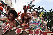 Tossing beads to the crowd from a float at the Dream Parade, Taipei.