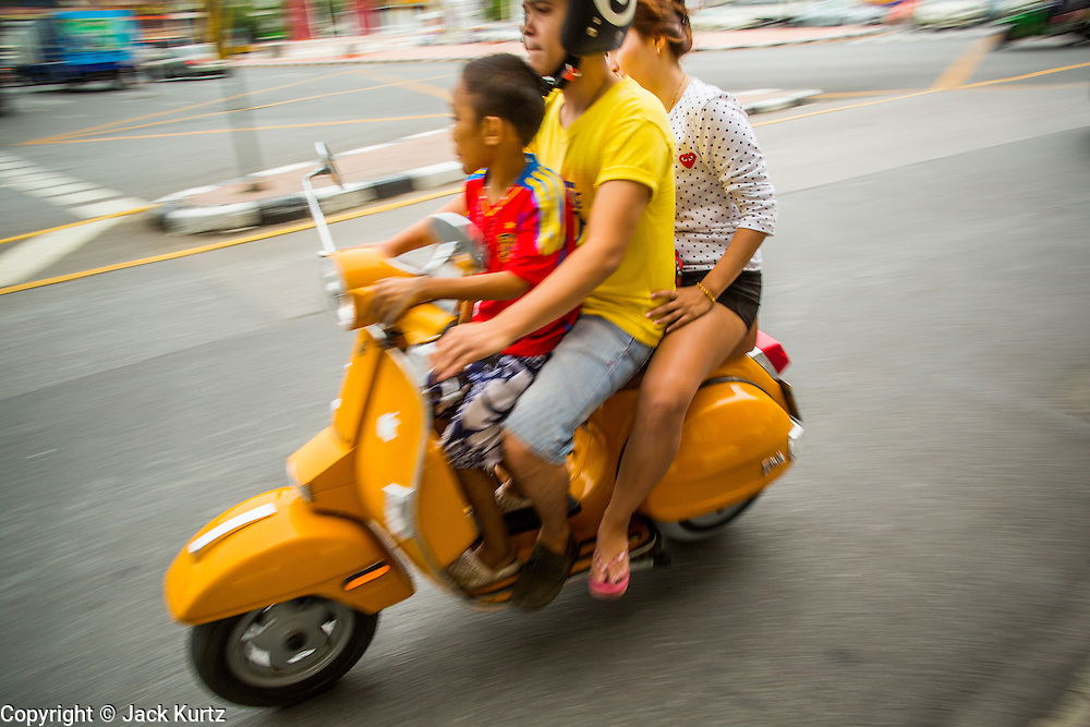 12 NOVEMBER 2012 - BANGKOK, THAILAND:   A family on a motor scooter on Bamrung Muang Street in Bangkok. Motor scooters and motorcycles are used for family transportation in the developing world. PHOTO BY JACK KURTZ