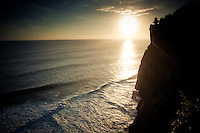 The suns sets over the Indian Ocean at Uluwatu Temple, Bali, Indonesia.