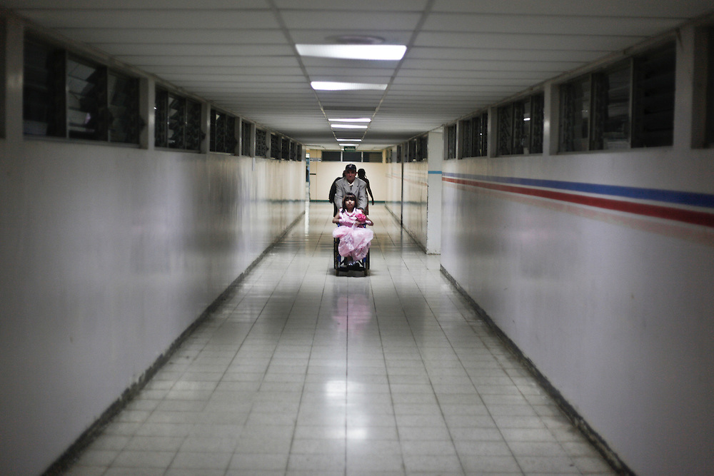 In this photo taken on Saturday, Aug. 27, 2011. A leukemia patient Maria Jose Martinez, fourteen  years old enters with her father in one of the main alleys at the Oncology area at the 'La Mascota' children hospital on her way to her room after the 'Quinceanera' celebration in Managua, Nicaragua. Maria Jose was admitted for her Treatment at La Mascota Hospital in May. 10 of 2011 until August. 29 of 2011, during that period she stayed one month at the intensive care unit. The Association of Parents of children with leukemia and Cancer in Nicaragua, Mapanica, have been organizing for their third year the 15 year old celebration of young girls that have been struggling with the cancer and they still are battling to win this fight against some type of cancer and leukemia at the Childrens hospital La Mascota, in Managua, Nicaragua.