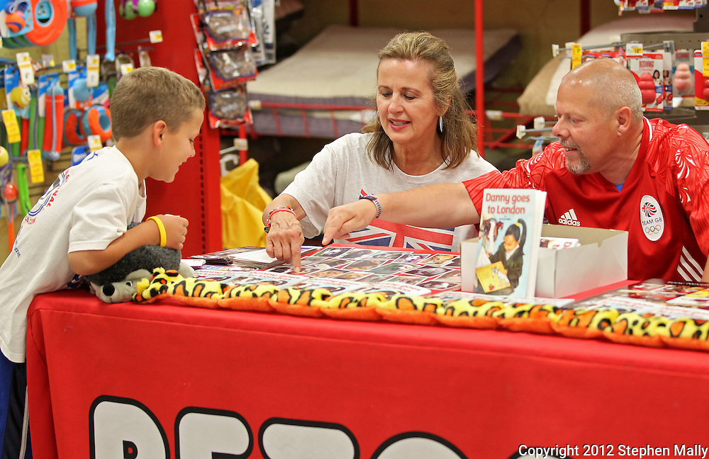 "Stevie Cain (from left), 8, of Cedar Rapids, Janet Holtman, of Cedar Rapids and Tony Nevett talk about the pictures of various dogs on the table at Petco, 1450 Twixt Town Road, in Marion on Saturday, August 4, 2012. Holtman is the president of Corridor Therapy Dogs and Nevett is the author of ""Danny goes to London."""