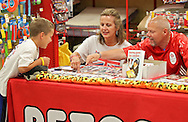 """Stevie Cain (from left), 8, of Cedar Rapids, Janet Holtman, of Cedar Rapids and Tony Nevett talk about the pictures of various dogs on the table at Petco, 1450 Twixt Town Road, in Marion on Saturday, August 4, 2012. Holtman is the president of Corridor Therapy Dogs and Nevett is the author of """"Danny goes to London."""""""