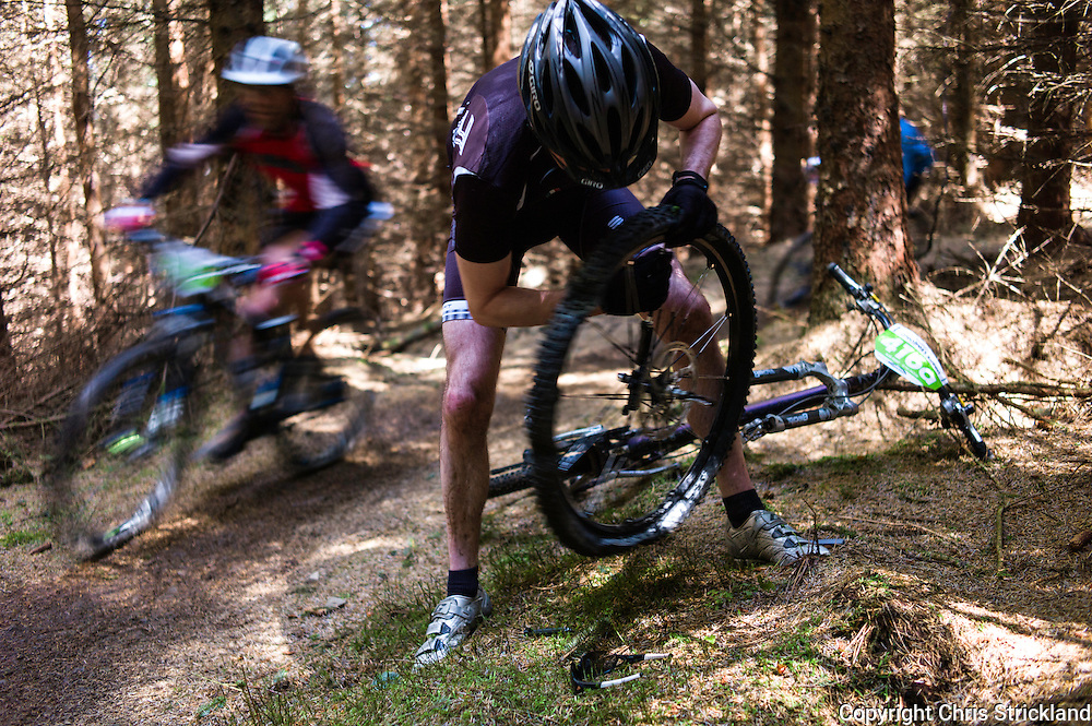 Glentress, Peebles, Scottish Borders, UK. 23rd May 2015. A mountain biker fixes a puncture at the Glentress 7 race during Tweedlove Festival. The aim is to complete as many laps of an 11km course during the 7 hour time limit.