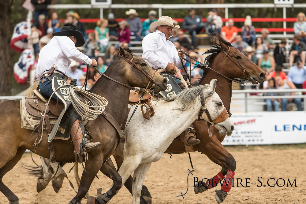 Pickup men Scott McClain, right, and Duane Gilbert get control of Summit Pro Rodeo's Wigwam during the third performance of the Elizabeth Stampede on Sunday, June 3, 2018.