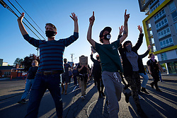 """Chanting """"Hands up, don't shoot,"""" protesters march with their hands raised during a June 3, 2020, Black Lives Matter protest in Eugene, Oregon. Participants were protesting the murder of George Floyd and other African-Americans by police."""