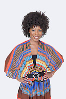 Portrait of beautiful African American woman in traditional wear standing over gray background