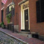 USA flag hangs above doorway of brownstone residence on historic river rock paved Acorn Street on Beacon Hill Boston MA