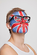 Pensive young Caucasian man with British flag painted on face wearing eyeglasses against white background