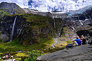 Tourists eat lunch and look at the the Rob Roy hanging Glacier, near Wanaka, New Zealand, Jan. 10, 2015. (Photo by David Lienemann)