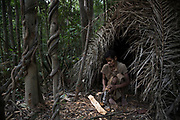 A Maniq elder cuts wood outside her hut.<br /> <br /> Evidence suggests that the Maniq, a Negrito tribe of hunters and gatherers, have inhabited the Malay Peninsula for around 25,000 years. Today a population of approximately 350 maniq remain, marooned on a forest covered mountain range in Southern Thailand. Whilst some have left their traditional life forming small villages, the majority still live the way they have for millennia, moving around the forest following food sources. <br /> <br /> Quiet and reclusive they are little known even in Thailand itself but due to rapid deforestation they are finding it harder to survive on the forest alone and are slowly being forced to move to its peripheries closer to Thai communities.